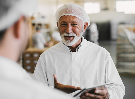 food worker in a lab coat and hair net holding a clipboard