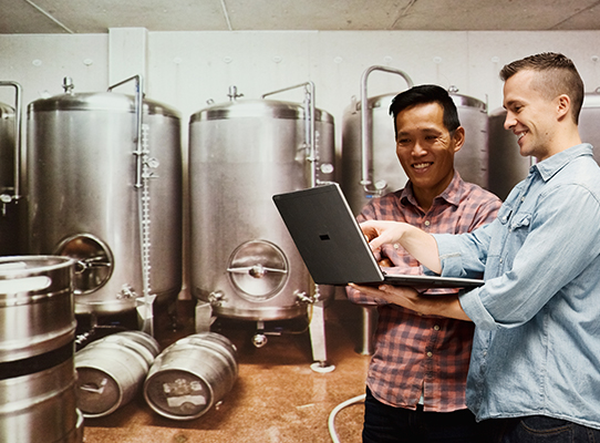 Two people looking at a laptop in a brewery